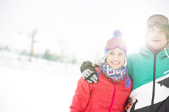Cheerful young couple standing arm around in snow Stock Images