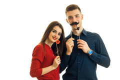 Cheerful young couple in the Studio with paper mustache laugh. Isolated on white background Royalty Free Stock Photos