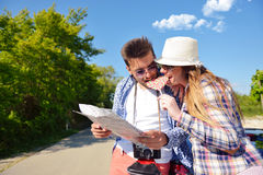 Cheerful young couple on a sunny day reading map.  Stock Photography