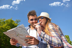 Cheerful young couple on a sunny day reading map.  Royalty Free Stock Image