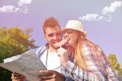 Cheerful young couple on a sunny day reading map.  Royalty Free Stock Photos