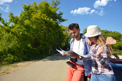 Cheerful young couple on a sunny day reading map.  Royalty Free Stock Photo