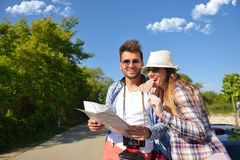 Cheerful young couple on a sunny day reading map.  Royalty Free Stock Photography