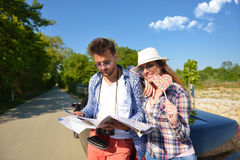 Cheerful young couple on a sunny day reading map.  Royalty Free Stock Images