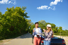 Cheerful young couple on a sunny day reading map.  Stock Photos