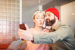 Cheerful young couple taking a humorous selfie with a smartphone. Romantic relationship between people. Cheerful young couple taking a humorous selfie with a stock photo