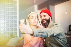 Cheerful young couple taking a humorous selfie with a smartphone. Romantic relationship between people. Cheerful young couple taking a humorous selfie with a stock photos