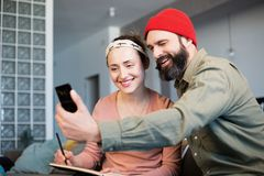 Cheerful young couple taking a humorous selfie with a smartphone. Romantic relationship between people. Cheerful young couple taking a humorous selfie with a stock images