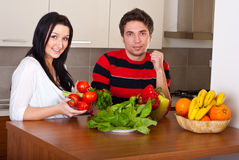 Cheerful young couple with vegetables in kitchen Stock Image