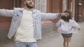 Cheerful young couple walk and fool around on urban street. Slow motion, Young cheerful couple in denim jackets walking along the building spreading their hands stock video footage
