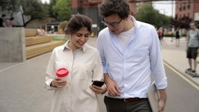 Cheerful young couple walking in the street, drinking coffee and talking stock video footage