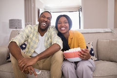 Cheerful young couple watching television while sitting on sofa at home Stock Photo