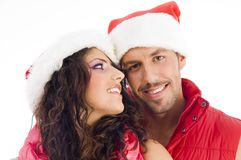 Cheerful young couple wearing christmas hat. Against white background Royalty Free Stock Image