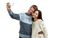Cheerful young couple wearing warm clothing taking selfie Stock Photos