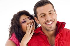 Cheerful young couple whispering to each other Stock Photography
