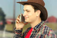 Cheerful young cowboy listening to the radio Royalty Free Stock Photos