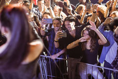 Cheerful young crowd photographing performer at nightclub. During music festival royalty free stock photo