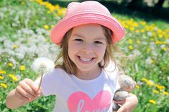 Cheerful young girl with dandelion. Cheerful young cute girl with dandelion on sunny field looking at camera Stock Photography