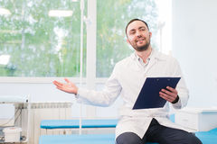 Cheerful young doctor holding a clipboard and gesturing with his hand at hospital ward Royalty Free Stock Image