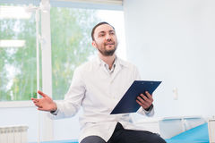 Cheerful young doctor holding a clipboard and gesturing with his hand at hospital ward Royalty Free Stock Photos