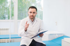 Cheerful young doctor holding a clipboard and gesturing with his hand at hospital ward Royalty Free Stock Images