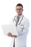 Cheerful young doctor with laptop smiling Stock Images
