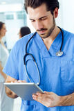 Cheerful young doctor looking at his digital tablet Royalty Free Stock Photos