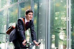 Cheerful young employee riding an utility bicycle in Berlin. Cheerful young employee with a healthy lifestyle riding an utility bicycle to a modern workplace in Royalty Free Stock Photo