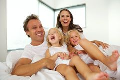 Cheerful young family with children relaxing on bed. Portrait of cheerful young family with children relaxing on bed and laughing royalty free stock images