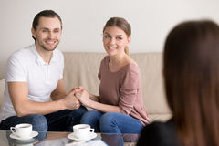 Cheerful young family couple on consultation. Holding hands and royalty free stock photos