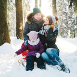Cheerful young family in the winter forest Royalty Free Stock Images