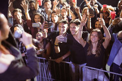 Cheerful young fans photographing performer at nightclub Royalty Free Stock Images