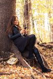 Cheerful young fashion female relaxing outdoors. And texting on cellphone stock photos