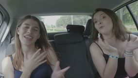 Cheerful young female best friends singing and dancing in the car on road trip celebrating freedom and having fun - stock video footage