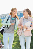 Cheerful young female college students walking in campus Stock Photos