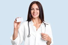 Cheerful young female doctor dressed in uniform, has stethoscope on neck, holds blank empty card for your advertisement or text, p stock images