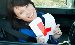 Cheerful young female driver tearing up her L sign Stock Photography