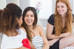 Cheerful young female friends chatting on sofa Royalty Free Stock Images