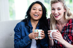 Cheerful young female friends with coffee cup Stock Photos