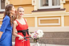 Cheerful young female friends are walking in town Stock Photography