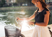 Cheerful young female at the park with her bicycle stock photos