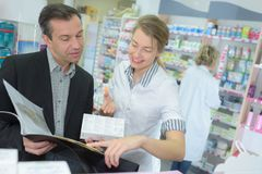Cheerful young female pharmacist helping customer. Cheerful young female pharmacist helping a customer Stock Photo