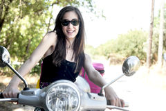 Cheerful young female on scooter Royalty Free Stock Image