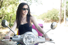 Cheerful young female on scooter Stock Photo