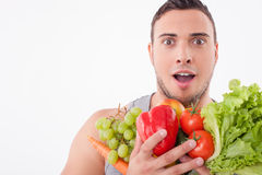 Cheerful young fit man likes healthy food. Handsome guy is standing and holding a heap of vegetables and fruits. He is looking forward with shock and smiling Stock Photos