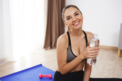 Cheerful young fitness girl make yoga execises on floor and drink water Royalty Free Stock Photos