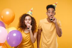 Cheerful young friends couple african american guy girl in birthday hat isolated on yellow background. Holiday party