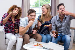 Cheerful young friends enjoying pizza Stock Photography