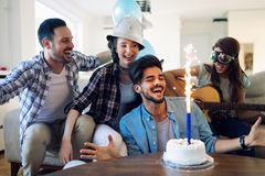 Cheerful young friends having fun on party stock photos