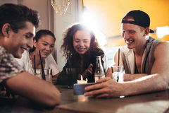 Cheerful young friends looking at smart phone Royalty Free Stock Photos